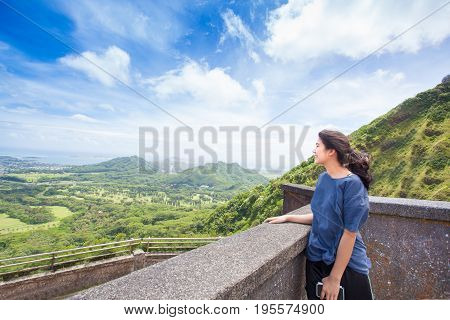 Biracial Asian Caucasian teen girl standing looking out over valley and hills of eastern Oahu Hawaii