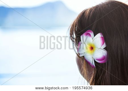 Dark haired girl wearing Hawaiian plumeria flower looking at ocean view and mountain.