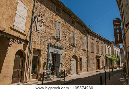Lourmarin, France - July 07, 2016. View of quiet alley with stone buildings and shops in the center of the lovely Lourmarin. Located in the Vaucluse department, Provence region, southeastern France