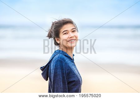 Smiling biracial Asian Caucasian teen girl in blue hoodie jacket standing on beach outdoors