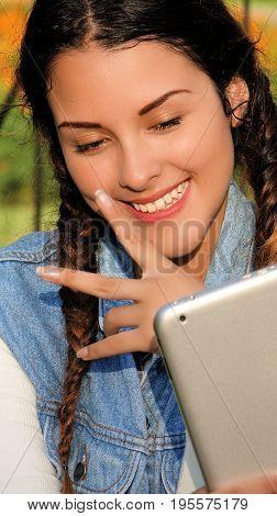 A Hispanic Teenage Girl Using A Tablet