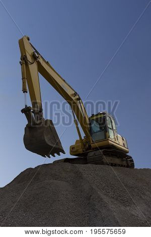Yellow Excavator working with blue sky bakground