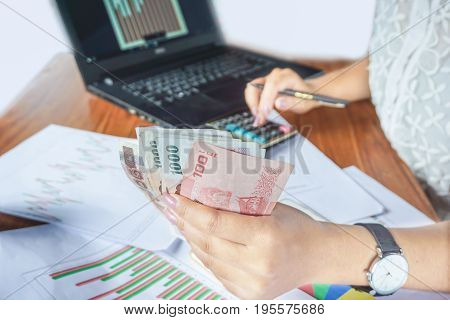businesswoman holding money while calculating and analyzing financial graph report with calculator and notebook on desk,business and finance background