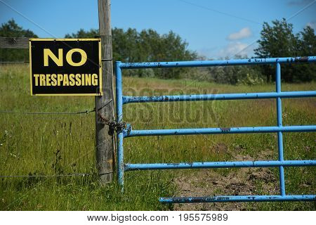 An image of an old yellow and black no trespassing sign hung on an old gate post.