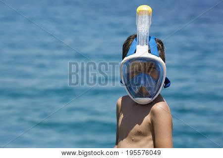 Snorkeler and coral reef, snorkeling man in full face mask, summer vacation activity, swimming in the warm tropical sea, seashore coral reef and fishes, starfishes near corals, Bali, Indonesia. Summer Vacation Fun