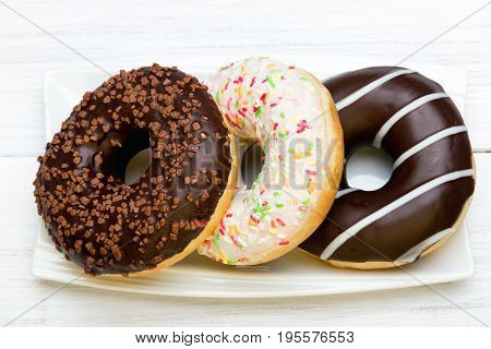 Tasty donuts with icing and chocolate on white wooden background copy space