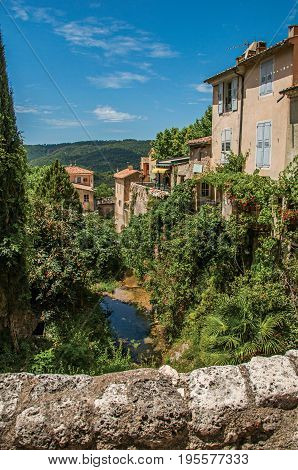 View of houses near creek and bluff with vegetation in the charming village of Moustiers-Sainte-Marie. In the Alpes-de-Haute-Provence department, Provence region, southeastern France