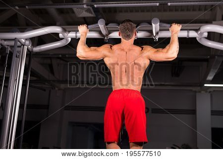Strong man doing pull ups. Muscular back of young bodybuilder training in dark background