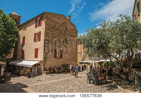 Moustiers-Sainte-Marie, France - July 08, 2016. People in their daily chores, on a street in the lovely village of Moustiers-Sainte-Marie. Provence region, southeastern France