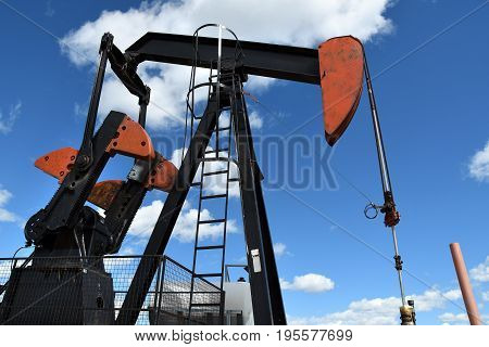 An image of a single red and black oil field pump jack.