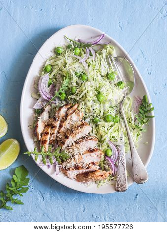 Salad with grilled chicken cabbage green peas and parmesan cheese. On a blue background top view