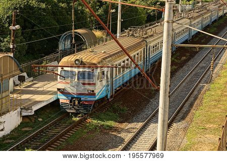 Train with passenger cars at an empty platform on the railway