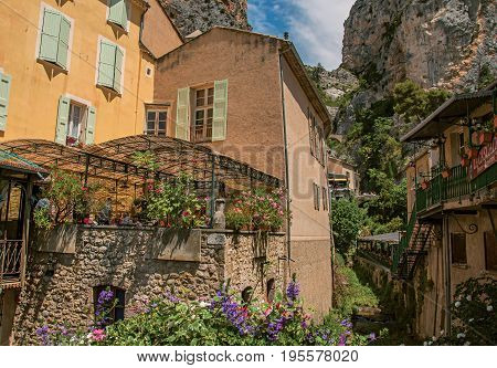 Moustiers-Sainte-Marie, France - July 08, 2016. Restaurant with flowers and cliffs in the lovely village of Moustiers-Sainte-Marie. Provence region, southeastern France