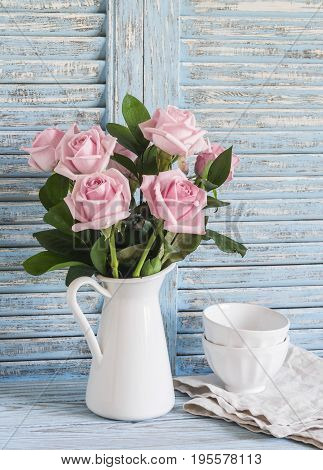 Pink roses in a white enameled pitcher and ceramic white bowls on blue wooden rustic background. Kitchen still life in vintage style