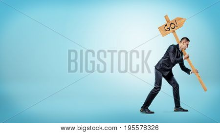 A businessman on blue background holding a heavy road sign with a 'Go' writing on it. Hard work. Right motivation. Road to success.