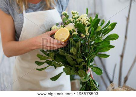Woman composes bouquet with lemon