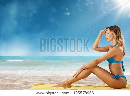 Girl in bikini sits on a tropical beach looking for new travel destination.