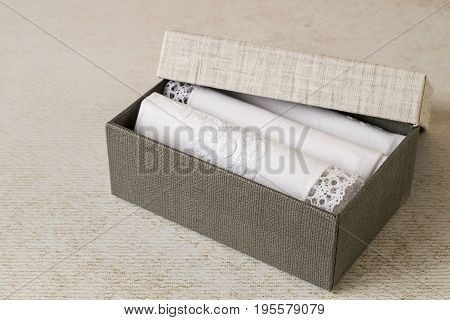 Accessories. A set of white handkerchiefs with decorative trim in a cardboard box on a light background. The idea for a gift. Selective focus.