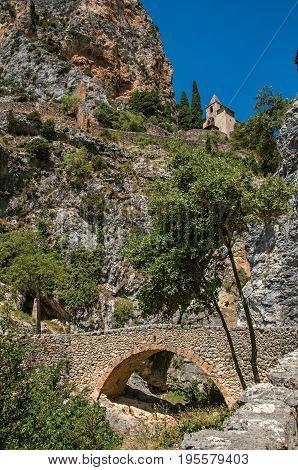View of the Notre-Dame de Beauvoir church amidst cliffs and rock bridge, above the graceful Moustiers-Sainte-Marie village. Alpes-de-Haute-Provence department, Provence region, southeastern France