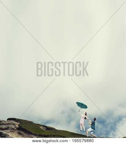 Woman taking off from the ground with an umbrella while boyfriend holds her on a mountain landscape.
