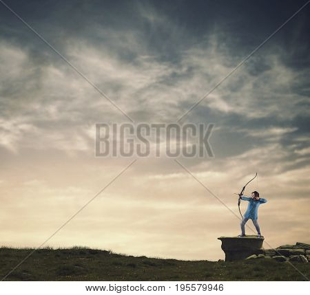 Woman shooting with a bow on a rock at sunset.