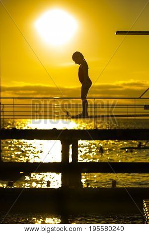 Indecision little girl silhouette on the 3m springboard. Preparing for jump into the sea in the summer evening. On background of beautiful sky with yellow sunset.