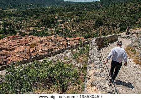 Moustiers-Sainte-Marie, France - July 08, 2016. Man walking down stone staircase with roofs of the Moustiers-Sainte-Marie village underneath. Provence region, southeastern France