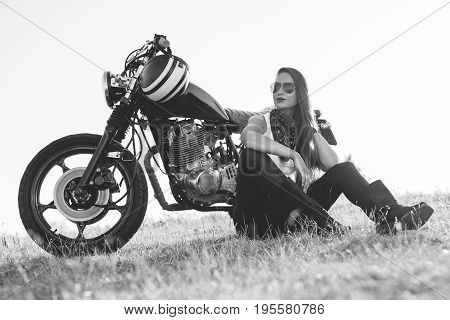 Black-and-white portrait of a beautiful biker woman sitting by her motorcycle