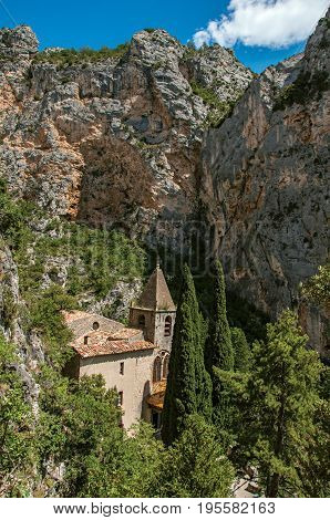 View of the church Notre-Dame de Beauvoir amid the cliffs, above the charming village of Moustiers-Sainte-Marie. In the Alpes-de-Haute-Provence department, Provence region, southeastern France