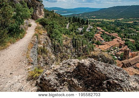 View of stone path above roofs and belfry in the charming village of Moustiers-Sainte-Marie. Located in the Alpes-de-Haute-Provence department, Provence region, in southeastern France.