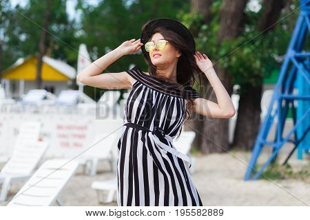 Luxury travel woman in black and white beachwear walking taking a stroll on sand summer beach. Girl tourist on summer holiday holding sun hat and yellow sunglasses at vacation resort.