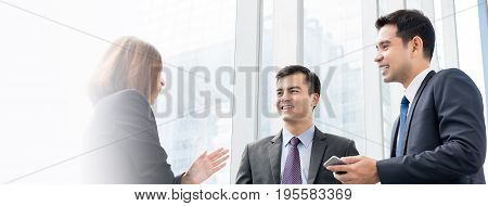 Group of business people talking at building hallway - web banner