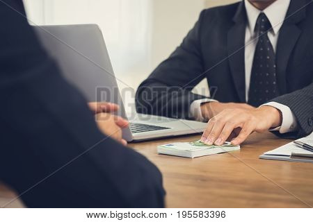 Businessman giving money Euro banknotes to his partner on working desk - loan bribery and corruption concepts