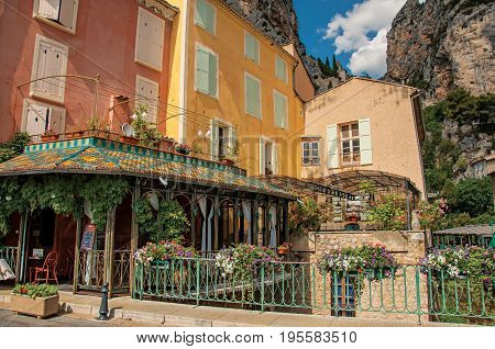 Moustiers-Sainte-Marie, France - July 08, 2016. Restaurant with flowers and cliffs in the village of Moustiers-Sainte-Marie. Alpes-de-Haute-Provence department. Provence region, southeastern France