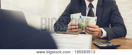 Businessman counting money Euro banknotes while making contract - panoramic banner