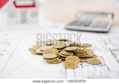 Money on blueprint paper with blurred house model and calculator in background - real estate loan and financial concepts