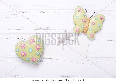 Decorative butterfliy heart and empty tag on vintage wooden background. Top view. Flat lay. Place for text.