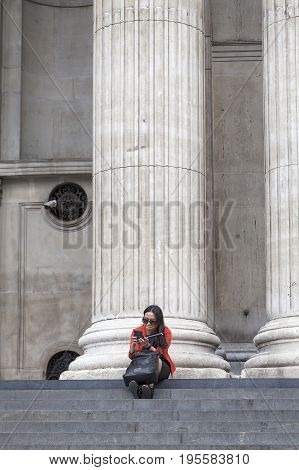LONDON UNITED KINGDOM - JUNE 22 2017: 18th century St Paul Cathedral majestic columns and woman sitting on the stairs. It is an Anglican monumental cathedral the seat of the Bishop of London