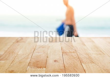 Wood table top with a man walking on the beach as blur background