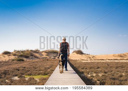 View from behind of a man walking with his dog on a road leading through beautiful landscape.