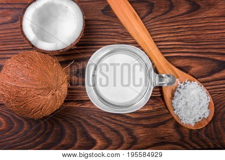 A mason jar full of fresh coco milk, a spoon with coconut chips and ripe coconuts on a dark brown wooden table.  Ripe, raw, fresh, healthy, organic and exotic nuts. Fresh and tasty coconut products.