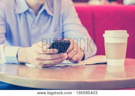 A man using smart phone with coffee cup on the table in coffee shop - vintage tone
