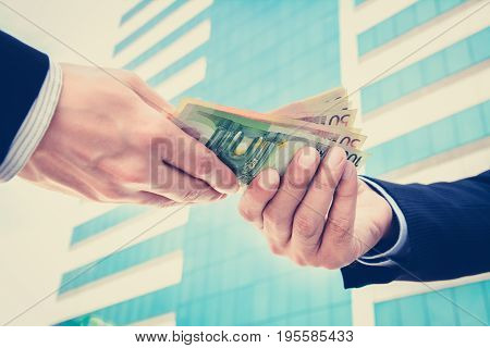 Businessman hands passing money Euro currency (EUR) - vintage tone