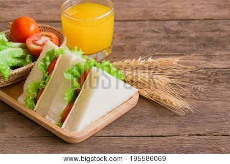 Triangle slice piece of sandwich ham cheese with lettuce and tomato on wood plate. Homemade sandwich ham cheese and vegetable for breakfast or lunch. Delicious ham cheese sandwich ready to served on wood table with fresh orange juice.