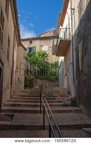 View of alley with houses, staircase and handrail at sunset, in the lovely village of Gréoux-les-Bains. Located in Alpes-de-Haute-Provence department, Provence region, southeastern France