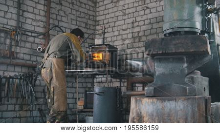 Craft beard man - muscular man working on a blacksmith with metal, wide angle