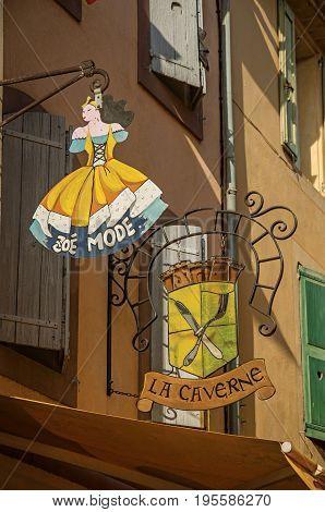 Gréoux-les-Bains, France - July 08, 2016. Close-up of a metallic street shop sign in a building at Gréoux-les-Bains village. Alpes-de-Haute-Provence department, Provence region, southeastern France