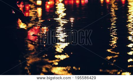 Blurred background - floating lighting water Lanterns on river at night, telephoto