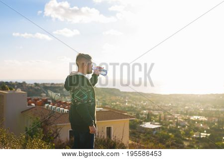 Young man standing on top of mountain with gorgeous view holding a bottle of mineral water. Enjoying drinks water.