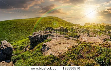 huge boulders on the edge of hillside at sunset. fine weather in summer mountain landscape with rainbow